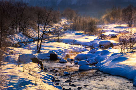 Sunrise on the river. Morning view of Hakuba Miyama river. Snow around three mountains of Hakuba Nagano prefecture, Japan.