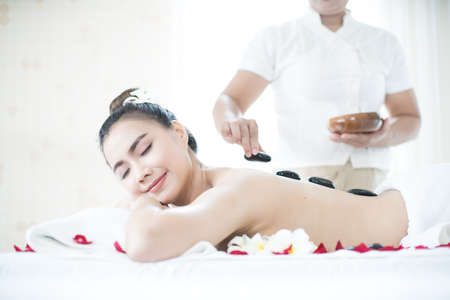 A young woman is spaing with hot stones at a spa shop in Bangkok, Thailand.