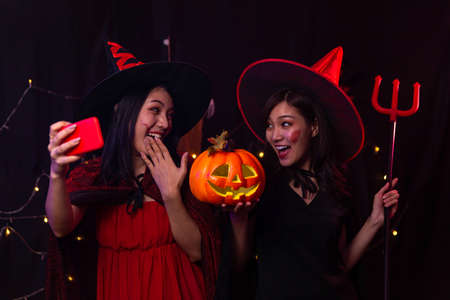 Young women using smartphones to take selfies at Halloween party. Stockfoto