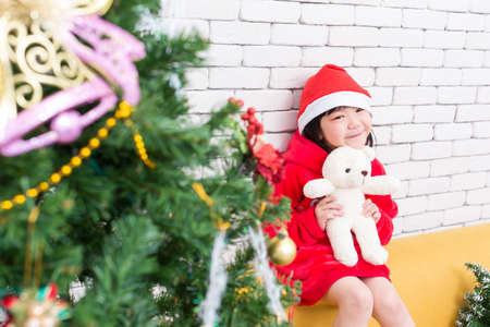A girl in a Christmas outfit holds a bear in a room decorated with a Christmas tree.