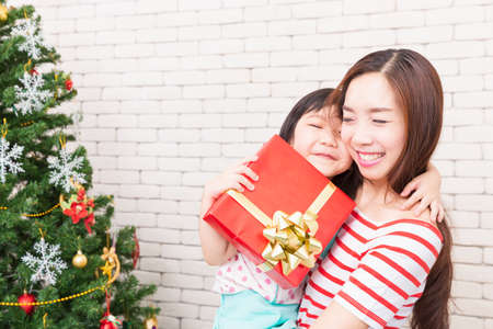 A girl and a mother holding a gift box in a room with a Christmas tree.