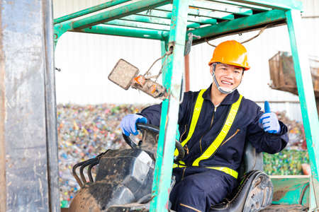Engineer driving a loader in the recycling plant. Staff thumbs up.