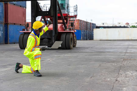 Foreman is giving a signal to work in the harbor. To move the cargo container onto the ship.