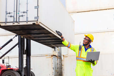 Foreman is controlling air or sea freight. Foreman works with laptop computer radio to communicate with forklift drivers. Stockfoto