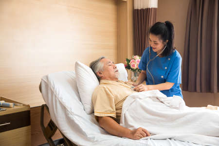 The doctor was listening to the heart of an elderly patient through a stethoscope. And in a hospital room. 免版税图像