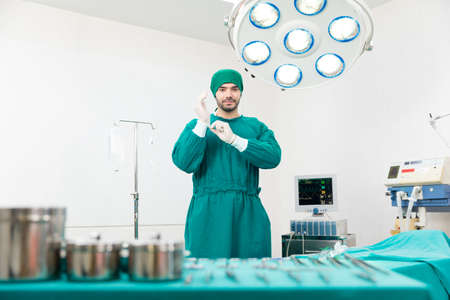 The surgeon is wearing gloves in an operating room equipped with modern medical equipment.