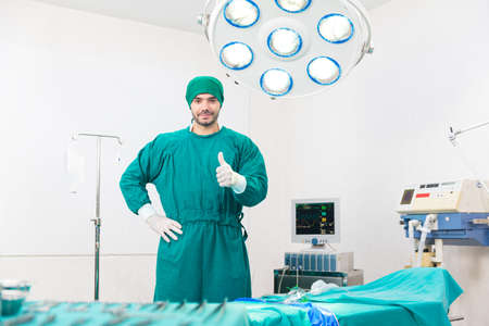 The surgeon is wearing gloves in an operating room equipped with modern medical equipment. Surgery doctors raise their thumbs. Surgery doctors holds an excellent thumb.