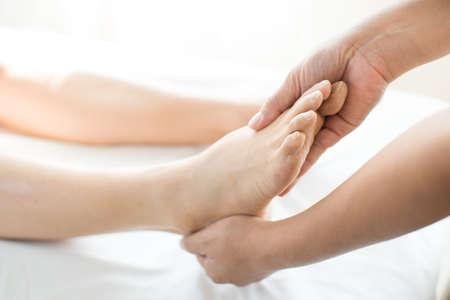 Young woman doing foot massage in spa massage parlor Stockfoto