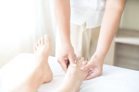 Foot massage. Close up of hands therapist's massaging female foot. Asian woman in wellness beauty spa having aroma therapy massage with essential oil. Thailand. Copy space.