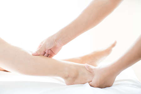 Young woman doing foot massage in spa massage. Foot massage. Close up of hands therapist's massaging female foot.