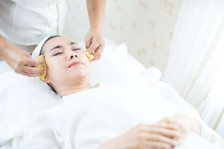 Young woman doing skin spa using mud and fruit in spa shop. Facial spa.