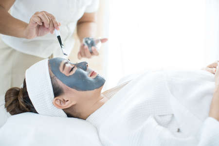 Face Skin Care. An Asian woman is masking her face in a spa salon. Woman with cosmetic spa facial mask. Thailand.