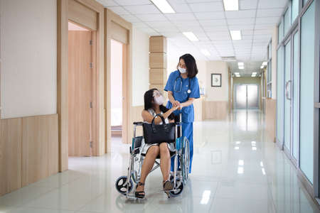 The hospital is encouraging the patient in the hospital corridor.
