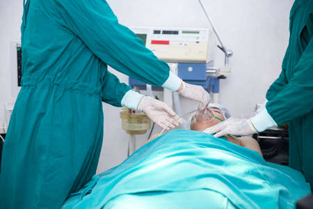 The surgeon is working on a ventilator for a patient in the emergency operating room. Stock Photo