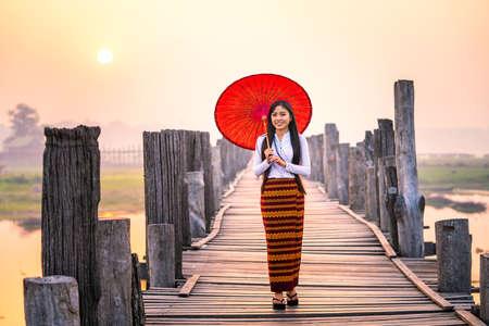 A young Burmese woman is walking with a red umbrella on the longest teak bridge in Asia.U-bein bridge, Mandalay, Myanmar. 스톡 콘텐츠