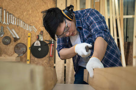 Carpenter measuring And cut wood to make furniture. The carpenters are working in a furniture factory.