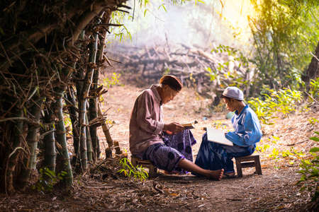 Muslim grandfather is teaching nephew to read a book. Muslims reading from the quran.