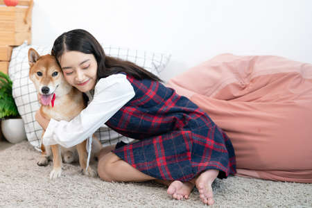An Asian woman lovingly hugs the Shiba Inu. Dog and girl in the living room.