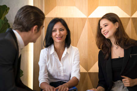 Co working space concept. Asian business looking and thinking in front of folder while stand at co-working space. young women and man working of new ideas in co-working space. Stock Photo
