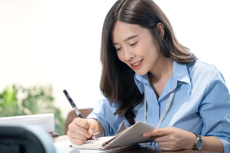 Employees are taking notes in the office. Smiling Asian businesswoman on phone at desk.