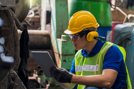 Technicians are customizing the operation of industrial machines with a tablet.