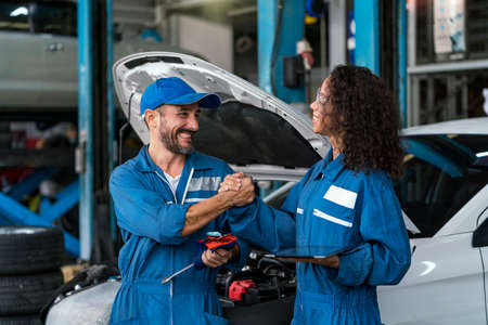 Two happy auto mechanics in uniforms working in auto service with car. Two men handshake mechanics in auto repair service.