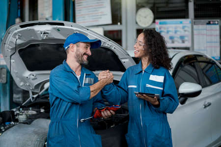 Smallbusiness. Two happy auto mechanics in uniforms working in auto service with car. Two men handshake mechanics in auto repair service.
