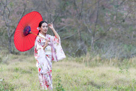 Japanese girl wearing a kimono holding a red umbrella. Beautiful Female wearing traditional japanese kimono with cherry blossom in spring, Japan. Asian woman tourists.