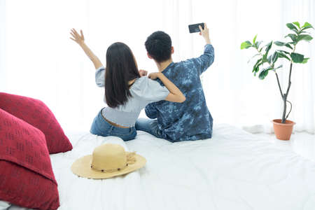Young Couple video call and going on vacation in a foreign country. Young Couple selfie happy and go on the travel. Asian female and male travel.