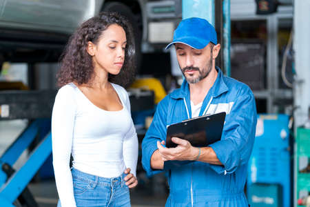 Service repair maintenance concept. The car mechanic is explaining the operation of the engine. Young woman looking at clipboard on hand mechanic at the garage.