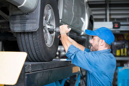 Service repair maintenance concept. Handsome worker in uniform changing car wheel. Male mechanic using rim wrench to fix car tire at auto repair shop.