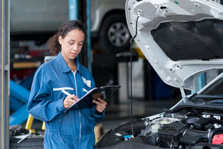Service repair maintenance concept. Mechanic female with clipboard checking car system at workshop. mechanic woman repairing car at garage.