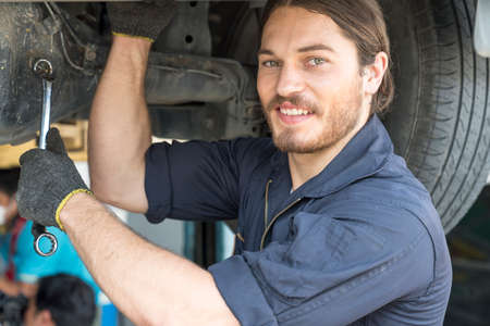 The mechanic is smiling happily at work. Mechanic reparing the car in the workshop garage. Auto mechanic hands using wrench to repair a car engine.