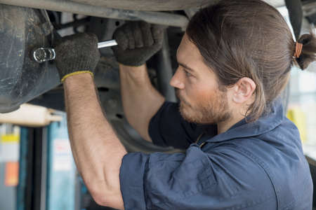 Auto mechanic hands using wrench to repair a car engine. Auto services and Small business concepts. Mechanic reparing the car in the workshop garage.
