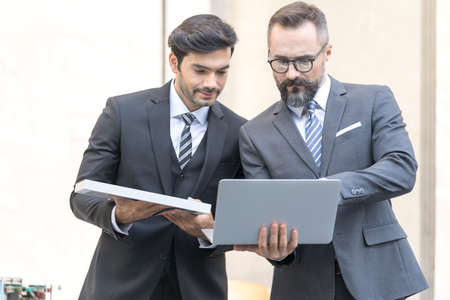 Handsome businessman and Engineer attractive. Businessman and attractive Engineer talking and holding laptop and solar panel. at outside office.