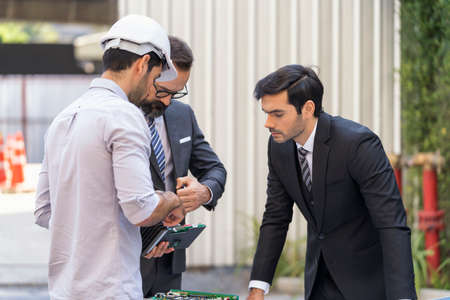 Businessman and attractive Engineer talking and discuss outside office. Engineer installing solar panels on a roof house for alternative energy photovoltaic safe energy.