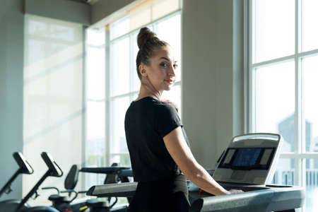 Fit women doing cardio workout and running on treadmill in sport club.