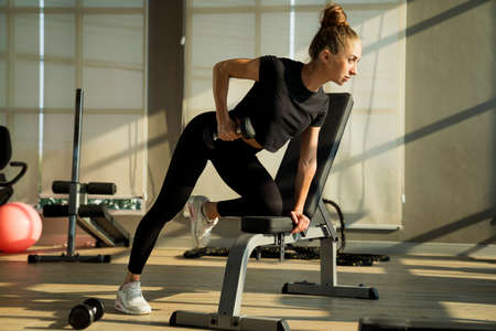 Concept fitness sport training lifestyle. Young woman lifting dumbbells. Active sport athletic woman with dumbbells pumping up muscles body. Stockfoto