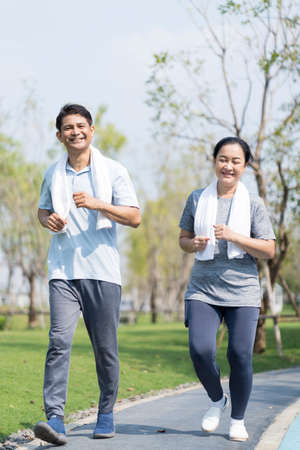 Couple doing exercising by running in the garden. Sporty mature couple styaing fit with sport.