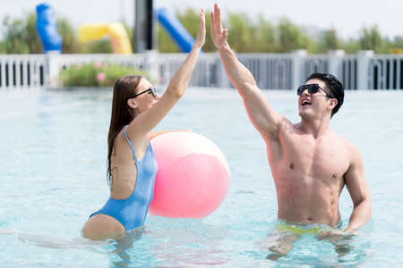 Couple has fun together while swimming in the pool. Couple into swimming pool with their hand.