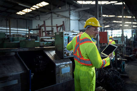 Engineers and skilled technicians are maintaining machinery. Professional technicians are holding a tablet to control machine in industrial plants. Stockfoto
