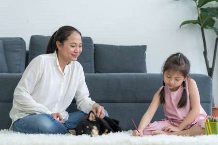 A mother is teaching her daughter to do homework in a living room with a black Shiba Inu.