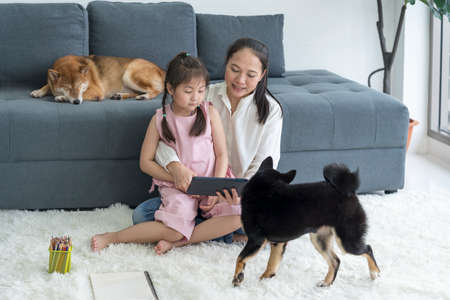 A mother teaches her daughter to do homework on a tablet computer in a living room with a Shiba Inu dog.