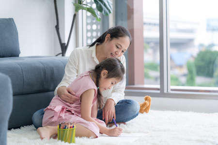 A mother teaches her daughter to do homework on a tablet computer in the living room.