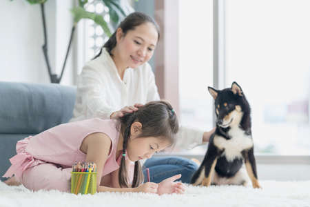 A mother teaches her daughter to do homework in the living room with a Shiba Inu dog.