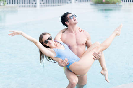 A young man holding a girl in the pool. Attractive young couple having fun in swimming pool.