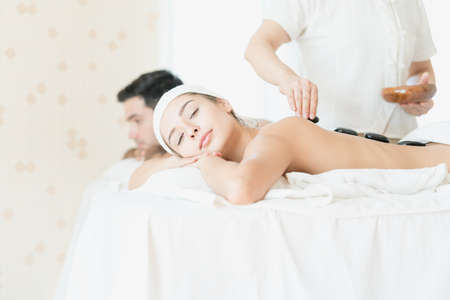 Male and Female massage therapist giving a massage at a spa. Woman having hot stones on her back in spa salon.