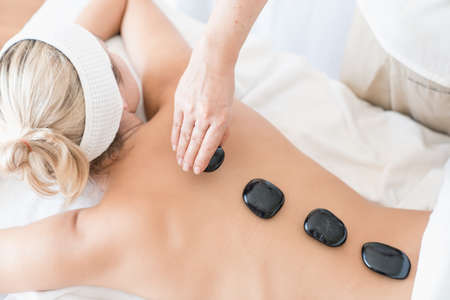Top view close up picture of young woman lying on massage table and receiving therapeutic spa procedure.