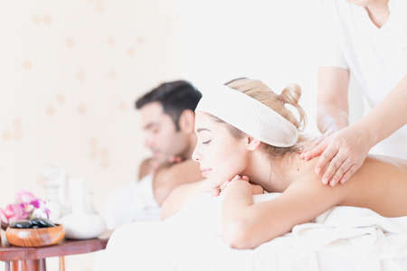 Young happy couple relaxing in spa salon. Couple in spa salon lying on the massage desks.
