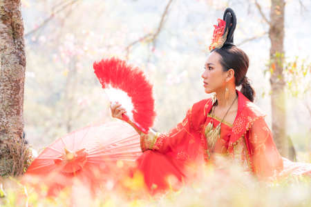 Chinese girl wearing Ancient chinese dress or Cheongsams dress Traditional Chinese dress, Young woman holding a fan and a red umbrella.
